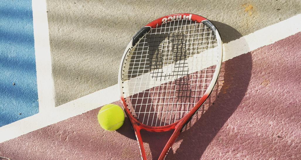 tennis racket and a tennis ball on a tennis court