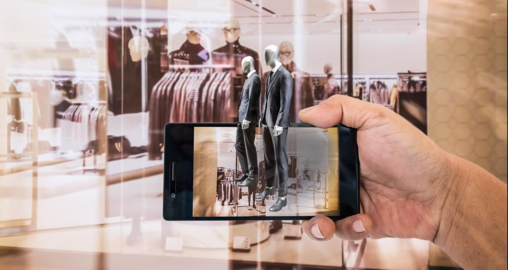 A person holds their phone using the augmented reality feature at a store