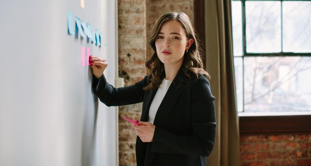 MM.LaFleur model wearing suit writing on whiteboard