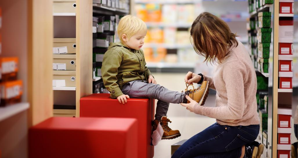 Woman helps boy try on shoes in store