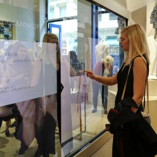 Woman in front of touch screen mirror at Rebecca Minkoff