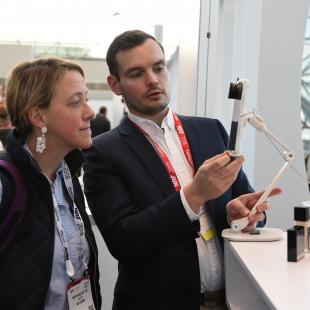 nrf 2018 innovation lab guy displays a technology device to a retailer
