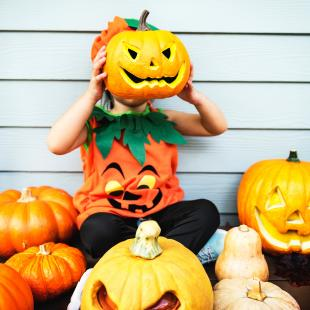 a child holds up a jack-o-lanter in front of his face for halloween
