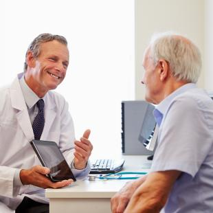 doctor and patient smile and look at screen together during visit
