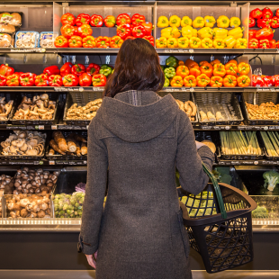 woman pondering choosing produce at a grocery store