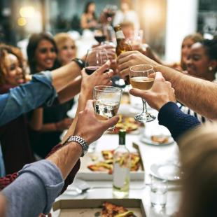 People cheer their wine glasses together at a restaurant over dinner