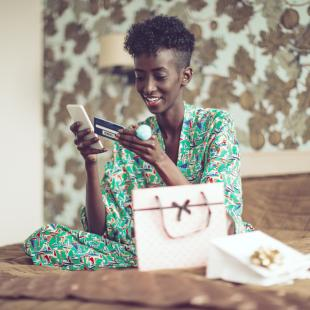 woman is sitting on her bed with her phone and credit card in hand getting ready to order something offline