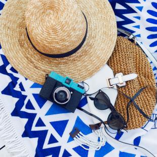 Straw hat, handbag, sunglasses and camera on a white wood background