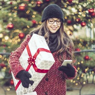 Young woman holds wrapped gift and looks at phone while holiday shopping