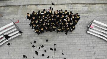 Group of kids stand outside in their cap and gowns after graduation