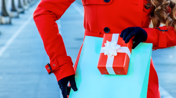 Woman holding a gift box in the winter during holiday season