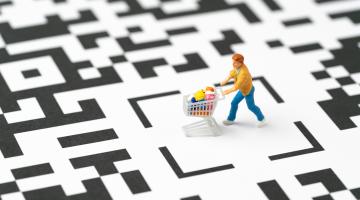 figure of a shopper pushing a cart over a QR code