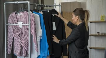 Woman going through clothes on a rack