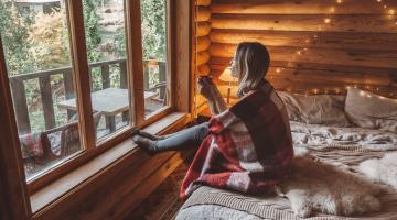 Woman in cosy log cabin looking outside holding mug
