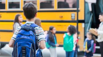Boy waits to get on school bus