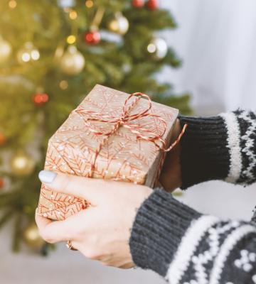 a lady is holding a christmas present in front of a christmas tree during the holiday season
