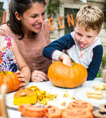 kids and their mom sit at a table outside and play with pumpkin carvings