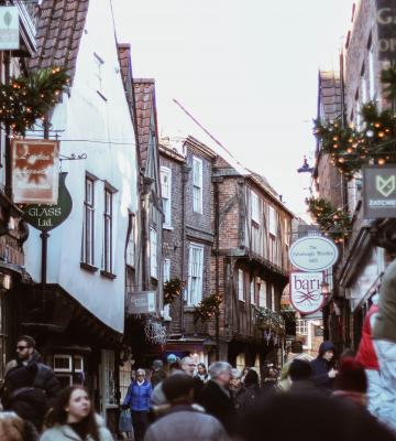 a town is shown during the holiday season with decorations and people shopping