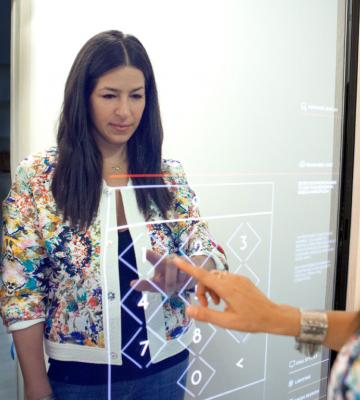 Woman using touchscreen mirror in dressing room