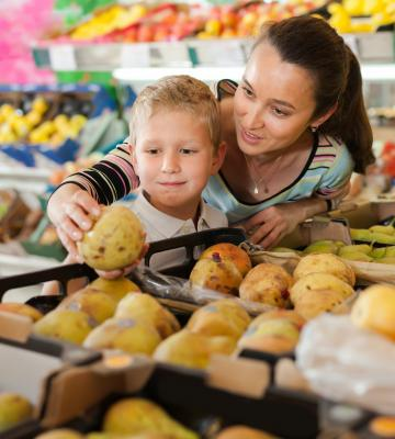 Mother and child shopping for groceries choosing fruit