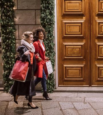 Two women walk down a street with shopping bags
